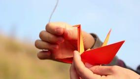 Origami, the art of origami. Origami crane. Small figures of origami cranes. Paper birds orange. Man frees origami crane. Origami on hand stock video footage