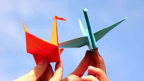 Origami, the art of origami. Little paper origami figure in his hand. Origami crane. Two paper birds in the hands of man. . Man playing with paper birds on the stock footage