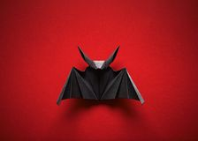 Origami bat on a red background Stock Photos