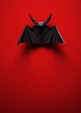 Origami bat on a red background. Black bat origami on a red background Royalty Free Stock Images