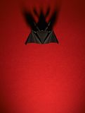 Origami bat on a red background Stock Images