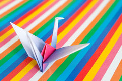 Origami bird on a colorful background. A single paper bird on a colorful stripes background. Shallow depth of field Stock Images