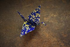Origami bird. Crane, swan made made of Japanese paper. Blue Indigo and gold colors of origami on rusty brown elegant background. stock photo