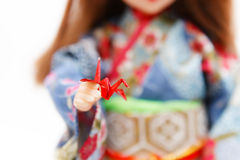 Origami bird and a Japanese doll in kimono. A Japanese doll in kimono presenting a miniature metallic red origami bird. Very shallow depth of field. Focus on the Royalty Free Stock Image