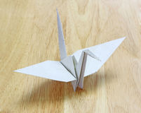 Origami Bird made of recycle paper on wood floor. Background Royalty Free Stock Photo