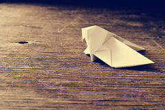 Origami bird on a wooden surface, retro effect Stock Photo