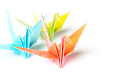 Origami birds. A group of 3 pastel colour paper birds on a white background stock image