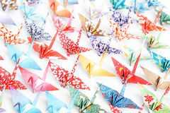 Origami birds. A group of origami cranes facing the same direction on a white background royalty free stock image