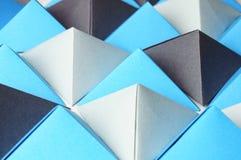 Origami blauwe en grijze piramides stock foto's
