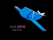 Origami blue airplane. Origami blue cartoon paper travel isolated airplane on a black background Stock Photography