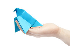 Origami. Blue dove sitting on the women's hand. Isolated object Stock Photo