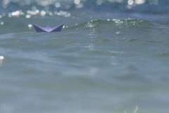 Origami boat riding on waves Royalty Free Stock Photos