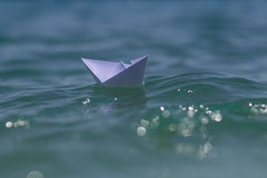 Origami boat riding on waves Stock Photography
