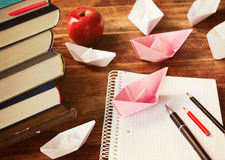 Education. Origami boats, books and notebook on the desk stock photos