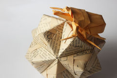Origami bug climbing over cyrillic sphere Stock Image
