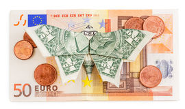 Origami butterfly sits on 50 euro banknote with coins isolated. Dollar origami butterfly sits on 50 euro banknote with coins isolated on white background Royalty Free Stock Photography