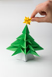 Origami - a Christmas tree. Placing the poinsettia a little green tree - origami stock photos