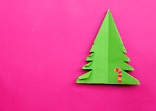 Origami Christmas tree paper on pink background. Stock Photo