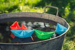 Origami color paper boats floating in washtube on water stock photos