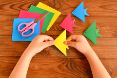 Origami colorful fish, paper sheets, scissors. Child holds paper sheet in his hands and making origami fish Stock Photo