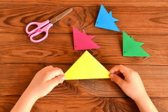 Origami colorful fish, scissors. Child holds paper sheet in his hands and making origami fish. Brown wooden background Stock Images