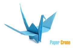 Origami crane. Traditional Japanese origami crane made from blue paper over white background stock image