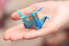 Origami crane on child hand. Child holding paper crane closeup Royalty Free Stock Images