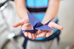 Origami crane in children's hands. (soft focused royalty free stock image