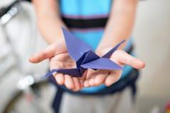 Origami crane in children's hands Royalty Free Stock Image
