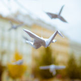 Origami crane flying in the city - street art. Guerilla art object - origami crane - in the city Stock Photo