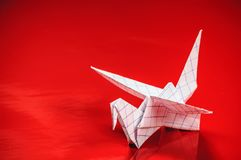 Origami crane on red. Background royalty free stock photography
