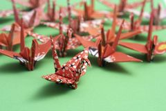 Origami cranes. A group of origami birds on a green background Stock Photo