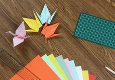 Origami cranes, colorful paper, cutting mat and pencil on wooden table Stock Images