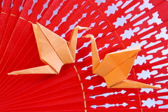 Origami Cranes from paper on red fan - Stock Photo. Origami Cranes from paper on red fan - Valentines Day or Wedding Card with orange  birds on wooden background Stock Images