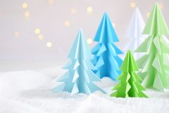 Origami 3D Xmas tree from paper on white background and bokeh lights. Merry Christmas and New Year card. Paper art style. Copy spa. Ce. Selective focus stock photography