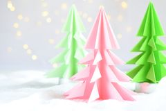 Origami 3D Xmas tree from paper on white background and bokeh lights. Merry Christmas and New Year card. Paper art style. Copy spa. Ce. Selective focus royalty free stock image