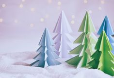 Origami 3D Xmas tree from paper on white background and bokeh lights. Merry Christmas and New Year card. Paper art style. Copy spa. Ce. Selective focus stock images