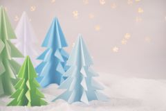 Origami 3D Xmas tree from paper on white background and bokeh lights. Merry Christmas and New Year card. Paper art style. Copy spa. Ce. Selective focus royalty free stock photo