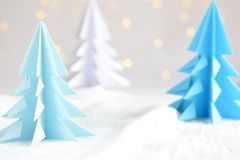 Origami 3D Xmas tree from paper on white background and bokeh lights. Merry Christmas and New Year card. Paper art style. Copy spa. Ce. Selective focus stock photo