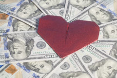 Origami di carta rossi del cuore e cento fondi delle banconote in dollari Immagine Stock