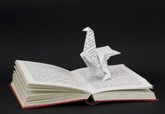 Origami dinosaur coming out of a book Stock Images