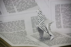 Origami dinosaur coming out of a book Royalty Free Stock Photos