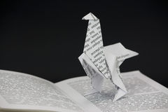 Origami dinosaur coming out of a book Royalty Free Stock Image