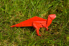 Origami dinosaur on grass. An origami dinosaur made of red paper on grass Stock Images