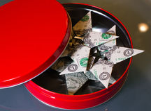 Origami dollar bill stars in red gift box. Origami dollar bill stars in elegant round red metal gift box with lid Stock Photo