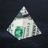 Origami dollar pyramid. Money symbol business on a black background Stock Image