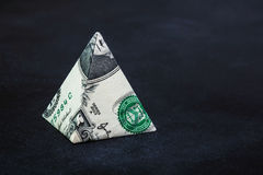 Origami dollar pyramid. Money symbol business on a black background Stock Photo