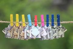 Origami dollar shirt on hanging nature green background stock images