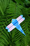 Origami - dragon fly. A photograph showing a cute childrens paper origami craft item of a folded dragonfly, in bright colors, placed on some green fern leaves as stock image
