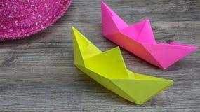 Origami, färgrika fartyg och rosa hatt på träbakgrund, hobby arkivbilder